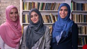 Tres mujeres árabes del hijab derecho están mirando la cámara que comienza con gran confianza y que sonríe, fondo de la bibliotec almacen de video