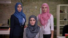 Tres mujeres árabes serias AR stading y que miran derecho el hihab que lleva de la cámara, ambientes de trabajo de Oriente Medio, almacen de video