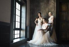 Tres mujeres acercan a los vestidos de boda de la ventana que llevan imagenes de archivo