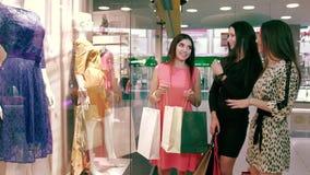 Tres mujeres amistosas jovenes que discuten sus compras almacen de metraje de vídeo