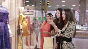 Tres mujeres amistosas que discuten los vestidos en el escaparate metrajes