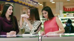 Tres mujeres atractivas en los vestidos hermosos que miran los accesorios en la joyería almacen de video
