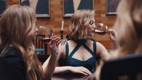 Tres mujeres atractivas en vestidos de cóctel que animan, vino rojo de consumición y teniendo una conversación en un pasado de mo metrajes