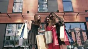 Tres mujeres atractivas que discuten su día de las compras almacen de metraje de vídeo