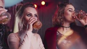 Tres mujeres atractivas que tienen una conversación amistosa con los vidrios de cóctel y beben una tostada feliz junta, moderno metrajes