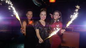 Tres mujeres bailan, se divierten y sostienen bengalas en Año Nuevo o la fiesta de Navidad almacen de video