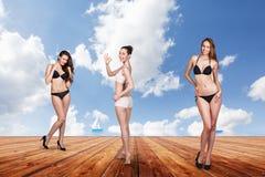 Tres mujeres bonitas jovenes que presentan en el embarcadero Imágenes de archivo libres de regalías
