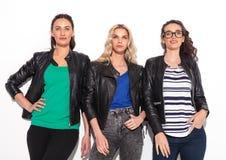 Tres mujeres casuales en las chaquetas de cuero que miran para arriba Fotos de archivo libres de regalías
