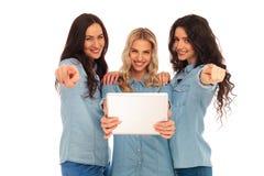 Tres mujeres casuales que sostienen una tableta están señalando los fingeres Fotos de archivo libres de regalías