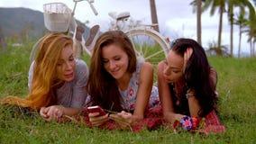 Tres mujeres compran algo con la tarjeta del smartphone y de crédito durante comida campestre almacen de metraje de vídeo