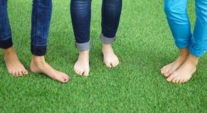 Tres mujeres con los pies desnudos que se colocan en hierba Foto de archivo