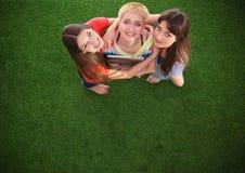 Tres mujeres con los pies desnudos que se colocan en hierba Imágenes de archivo libres de regalías