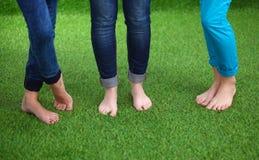 Tres mujeres con los pies desnudos que se colocan en hierba Fotografía de archivo libre de regalías