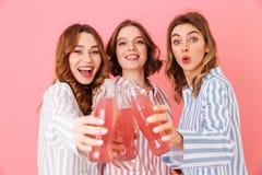 Tres mujeres contentas con buen humor en los pijamas rayados coloridos s Fotos de archivo libres de regalías