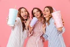 Tres mujeres contentas con buen humor en los pijamas rayados coloridos s Fotografía de archivo libre de regalías