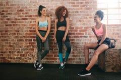 Tres mujeres de la raza mixta que se relajan en gimnasio foto de archivo