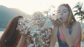 Tres mujeres de los amigos que soplan brillo colorido en la playa en la puesta del sol almacen de video