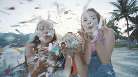 Tres mujeres de los amigos que soplan brillo colorido en la playa en la puesta del sol metrajes