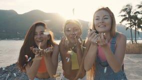 Tres mujeres de los amigos que soplan un espray del confeti en la playa en la puesta del sol almacen de metraje de vídeo