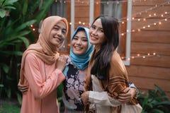 Tres mujeres del Islam que se colocan en el patio trasero mientras que mirada en la cámara imagenes de archivo