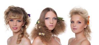 Tres mujeres descubiertas jovenes con estilo de pelo de la flor Imagenes de archivo