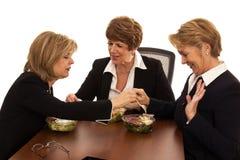 Tres mujeres disfrutan del almuerzo de negocios juguetón Foto de archivo