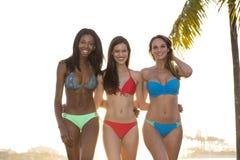 Tres mujeres en caminar del bikini, detrás encendido Foto de archivo