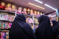 Tres mujeres en chodor negro eligen una bufanda en la tienda fotografía de archivo