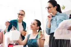 Tres mujeres en la fábrica de la ropa Están eligiendo las cremalleras para el vestido imagen de archivo libre de regalías