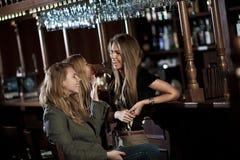 Tres mujeres en un club nocturno que se sienta en la barra Imagen de archivo