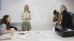 Tres mujeres están comunicando en una sala de reunión de la tienda de ropa metrajes