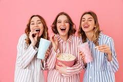 Tres mujeres felices en homewear que comen palomitas de maíz y que beben soda Foto de archivo libre de regalías