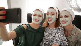 Tres mujeres felices jovenes con las mascarillas que toman el selfie en el balneario Amistad y concepto del bienestar, belleza de almacen de video