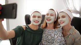 Tres mujeres felices jovenes con las mascarillas que toman el selfie en el balneario Amistad y concepto del bienestar, belleza de almacen de metraje de vídeo