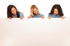 Tres mujeres felices que miran abajo al tablero en blanco grande Fotografía de archivo libre de regalías