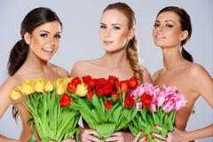 Tres mujeres hermosas con los tulipanes frescos de la primavera Foto de archivo