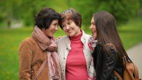 863a88ce7 Tres mujeres hermosas con sonrisa encantadora están abrazando la colocación  al aire libre en el parque