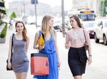 Tres mujeres hermosas de la moda que caminan en la calle Imagen de archivo libre de regalías