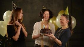 Tres mujeres hermosas en casquillos divertidos en el partido Uno de ellos que sostienen la torta de chocolate Muchacha del cumple almacen de metraje de vídeo