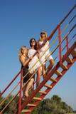 Tres mujeres hermosas jovenes en una escalera Imagenes de archivo