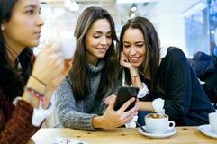 Tres mujeres hermosas jovenes que usan el teléfono móvil en la tienda del café Fotos de archivo libres de regalías