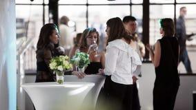 Tres mujeres hermosas que beben el champaigne, hablando el uno al otro en el restaurante metrajes