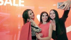 Tres mujeres hermosas que se oponen a fondo rojo y que toman la imagen de ellos mismos metrajes