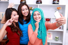 Tres mujeres hermosas que toman las fotos usando cámara del móvil foto de archivo libre de regalías