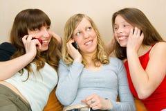 Tres mujeres jovenes con los teléfonos Imagen de archivo libre de regalías