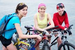 Tres mujeres jovenes en la bicicleta Fotografía de archivo libre de regalías