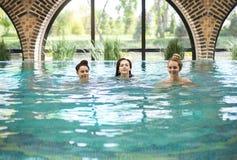 Tres mujeres jovenes en la piscina Fotografía de archivo libre de regalías