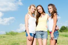 Tres mujeres jovenes felices que abrazan contra el cielo azul Imágenes de archivo libres de regalías