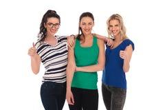 Tres mujeres jovenes felices que muestran la autorización manosean con los dedos encima de muestra Fotografía de archivo libre de regalías