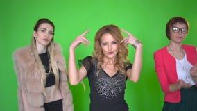 Tres mujeres jovenes hermosas en la ropa elegante dansing en la cámara en fondo de pantalla verde metrajes